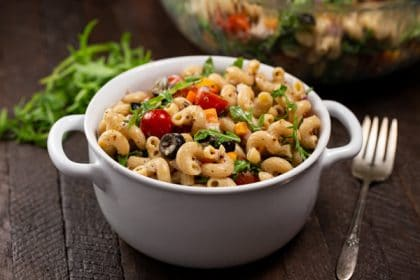 A pasta salad with lots of fresh veggies such as cherry tomatoes, arugula, bell pepper, and black olives- in a white bowl.