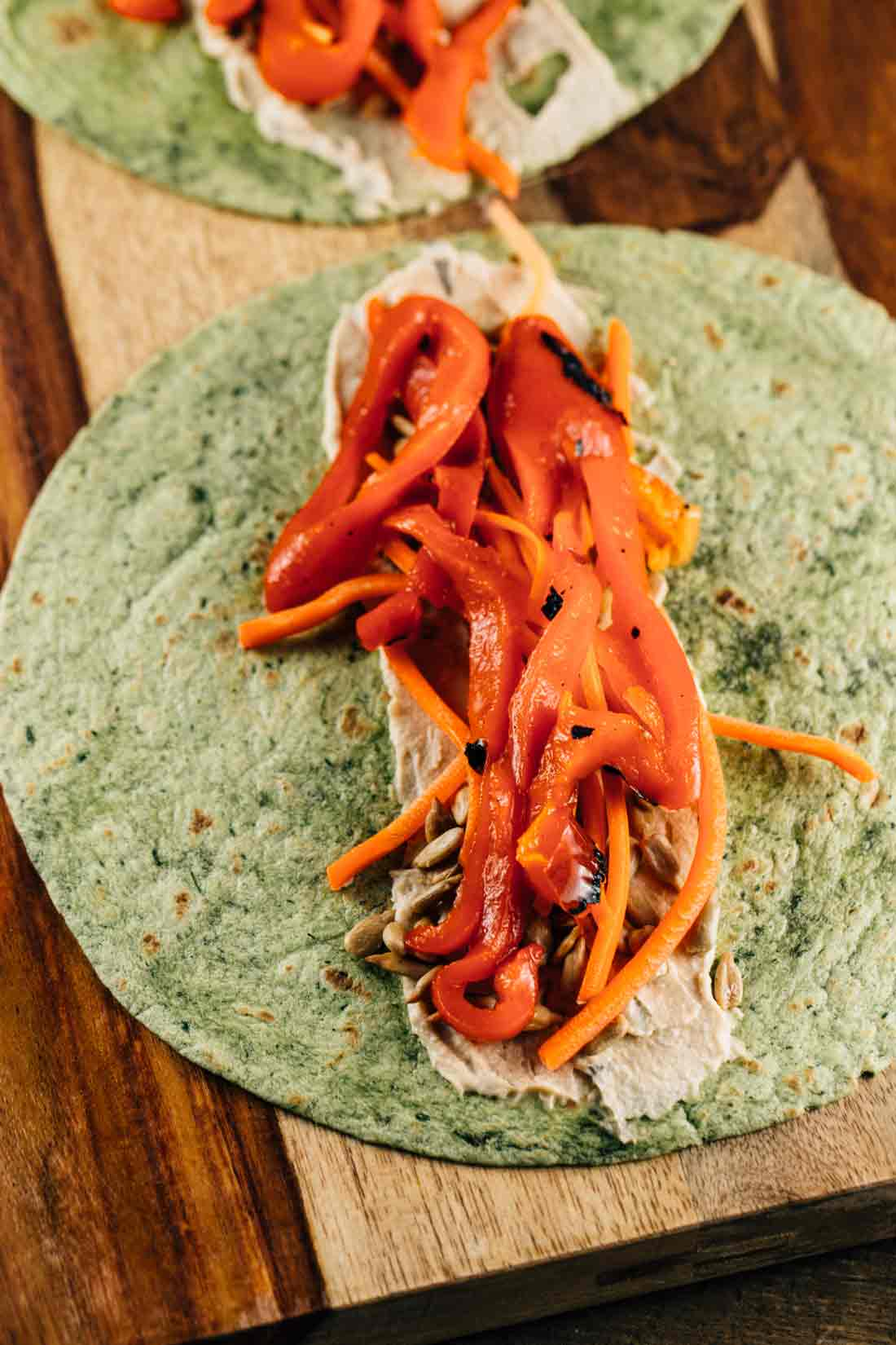 A spinach tortilla, with a layer of hummus, sunflower seeds, and roasted red peppers.