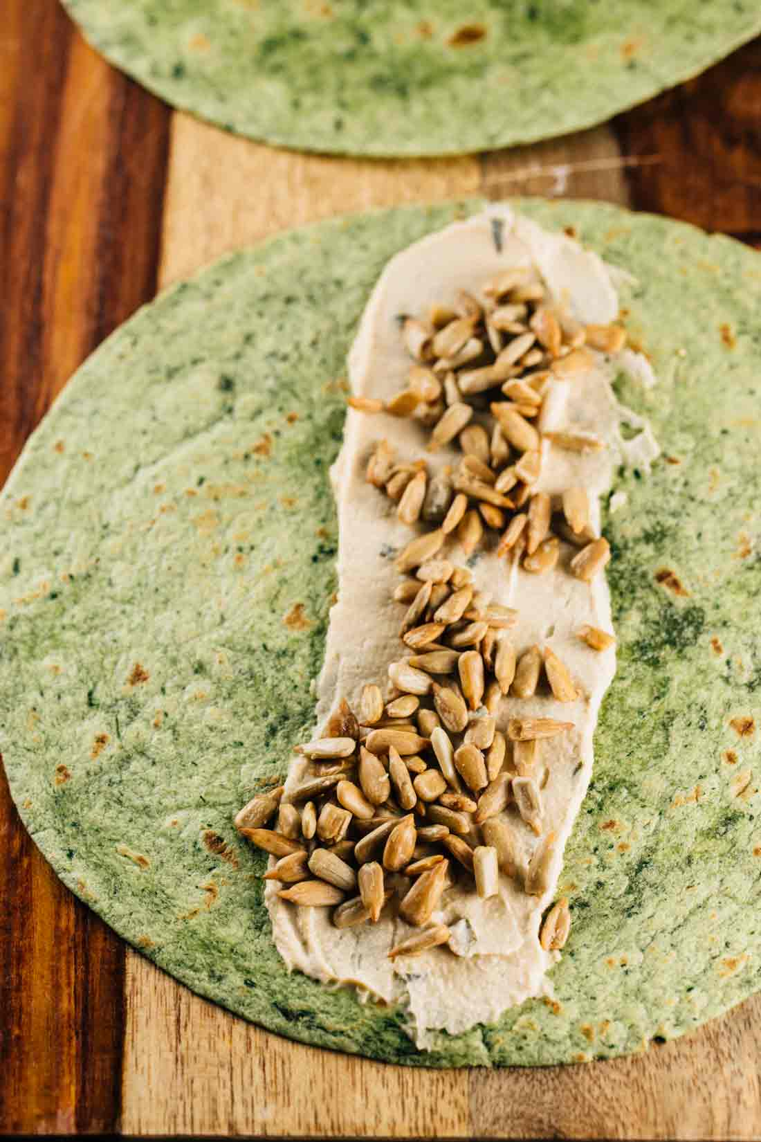 A spinach tortilla with a layer of hummus and sunflower seeds on top.