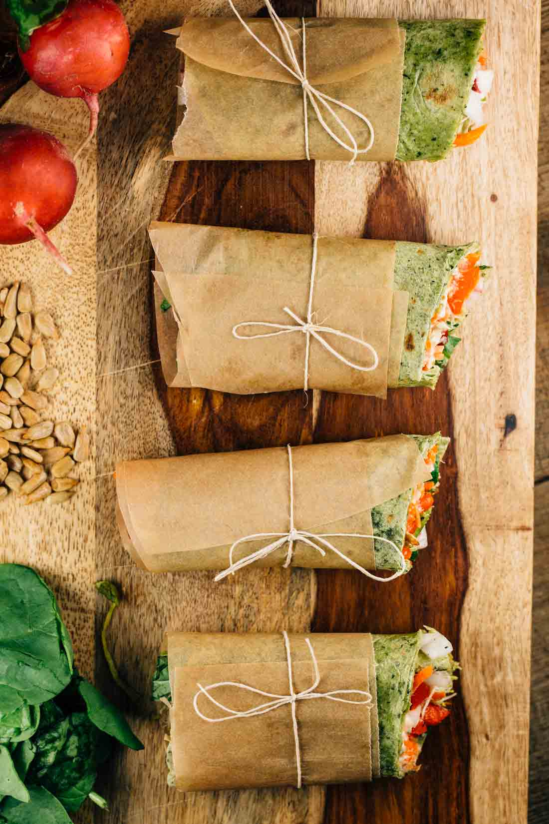An overhead shot of Sunflower Hummus wraps, wrapped in parchment paper, on a cutting board.