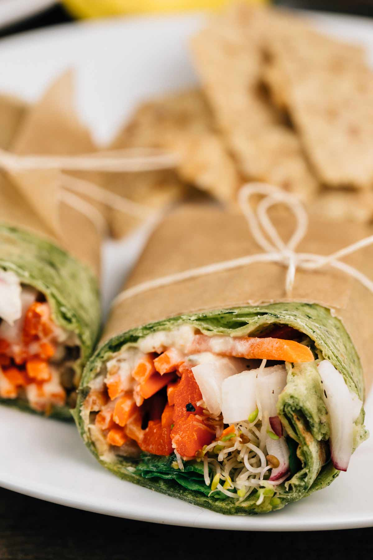 Sunflower Seed Hummus Wraps on a white plate, wrapped in parchment paper and tied with a string.