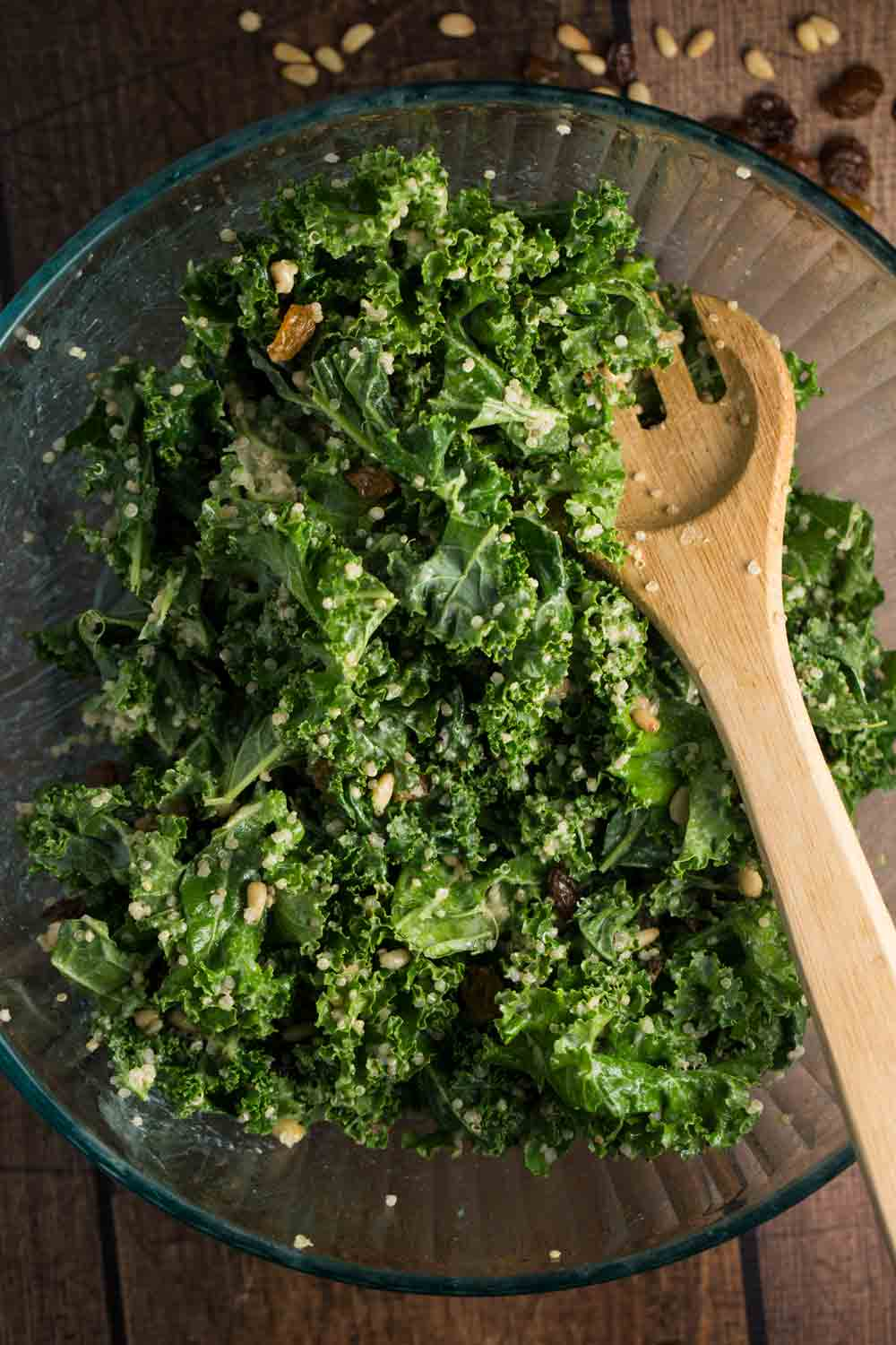 A large glass bowl filled with Kale Quinoa salad and a large wooden spoon.