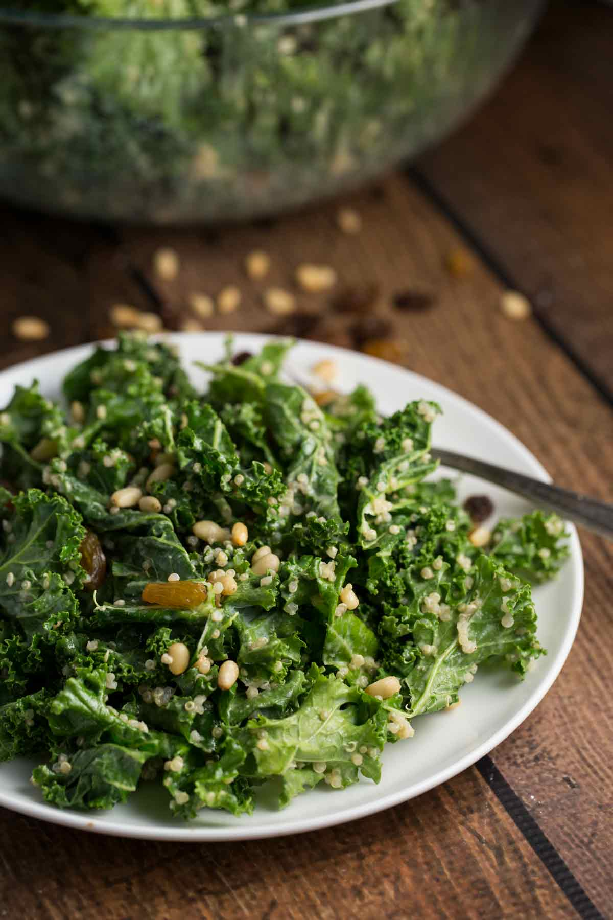 A white plate with a kale salad on top with quinoa and golden raisins.
