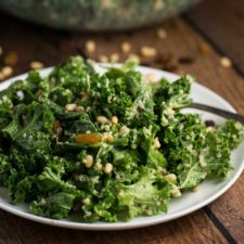 A white plate with a Kale Quinoa salad on top, with toasted pine nuts and a fork on the side.