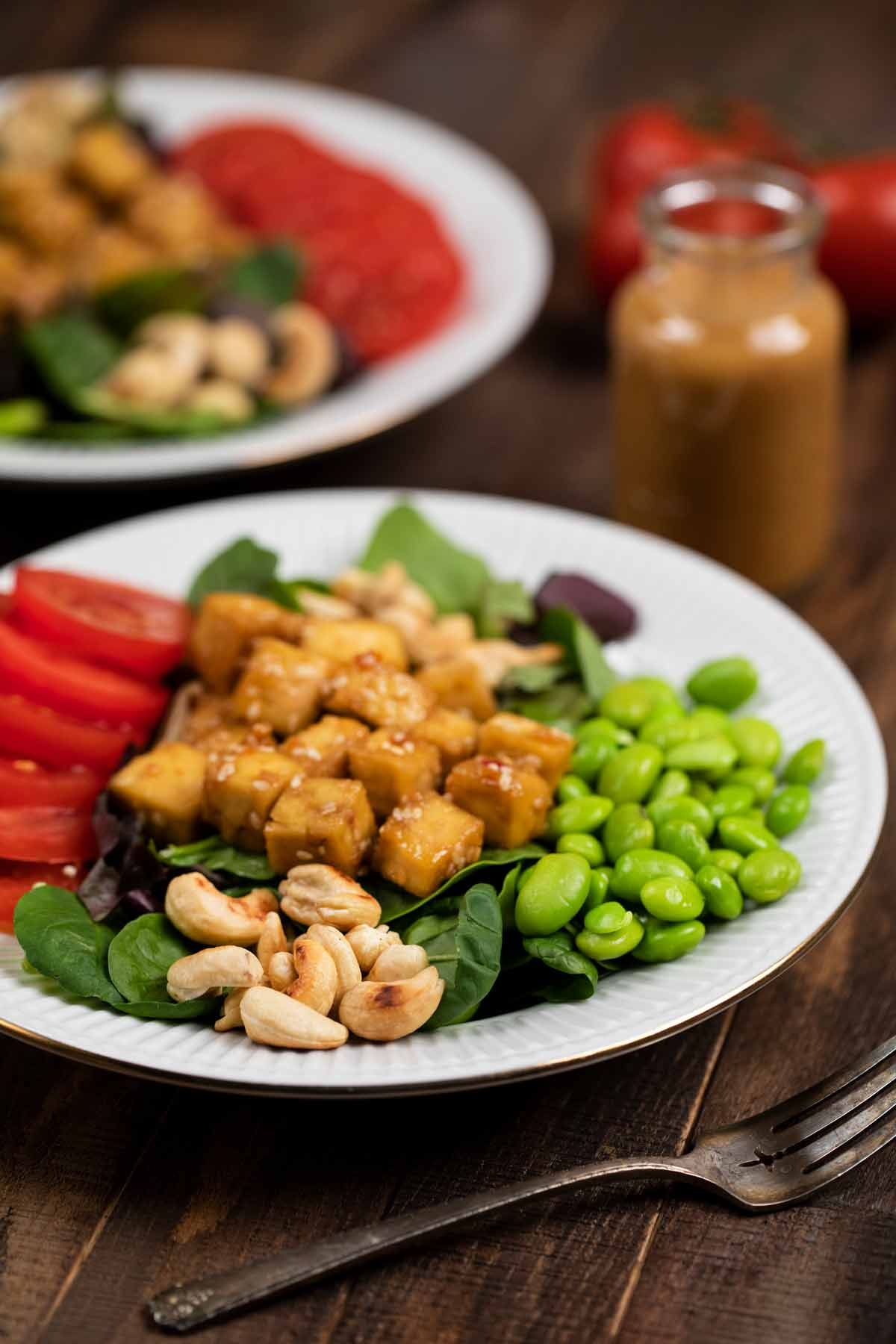 Crispy Sesame Tofu Salad on a white plate with edamame, tomatoes and roasted cashews.