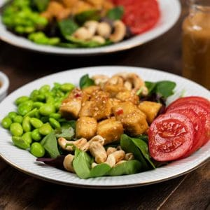 A bowl of crispy sesame tofu salad with tomatoes, edamame and tofu.