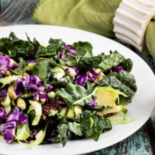 Superfood salad with veggies on a white plate with dressing on the side.