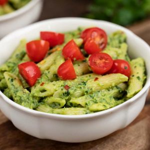 A white bowl filled with avocado penne pasta topped with cherry tomatoes.