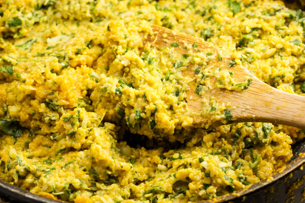 An extreme closeup of a pan filled with polenta mixed in with artichoke pesto.