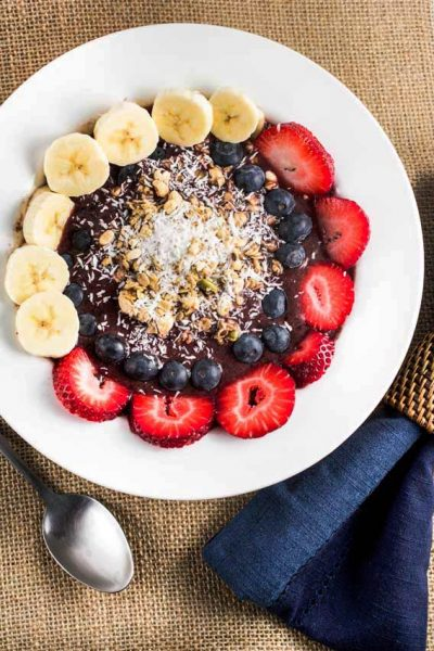 A bowl of acai with fresh strawberries, blueberries and bananas, topped with coconut and granola and a blue napkin.