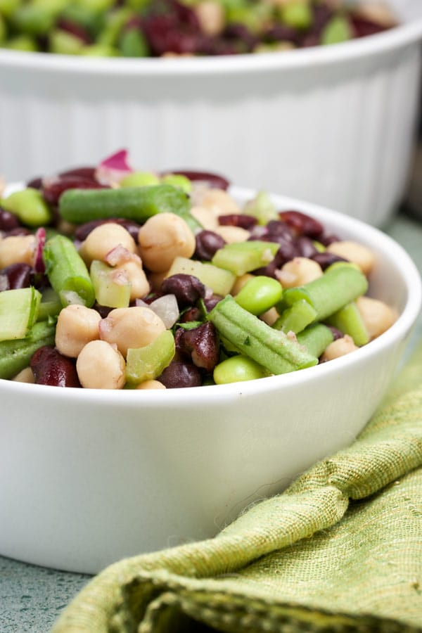 A salad of a variety of different types of beans in a large white bowl.