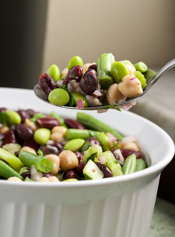 5 Bean Salad in a large white bowl, being scooped out with spoon.