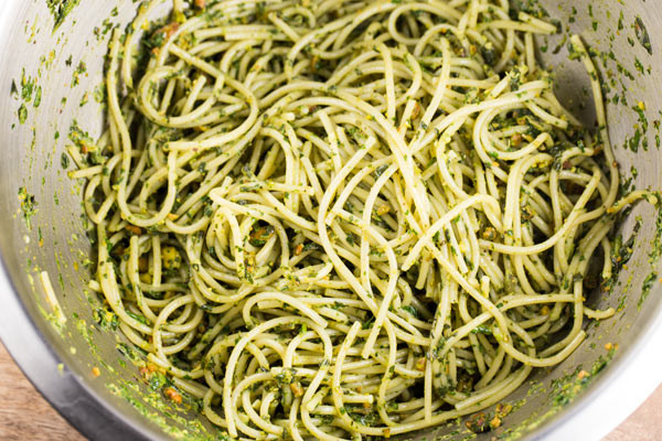 A large stainless steel mixing bowl filled with pistachio pesto pasta.