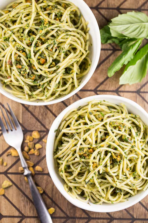 An overhead shot of 2 bowls of pistachio pesto pasta with fresh basil and a fork nearby.