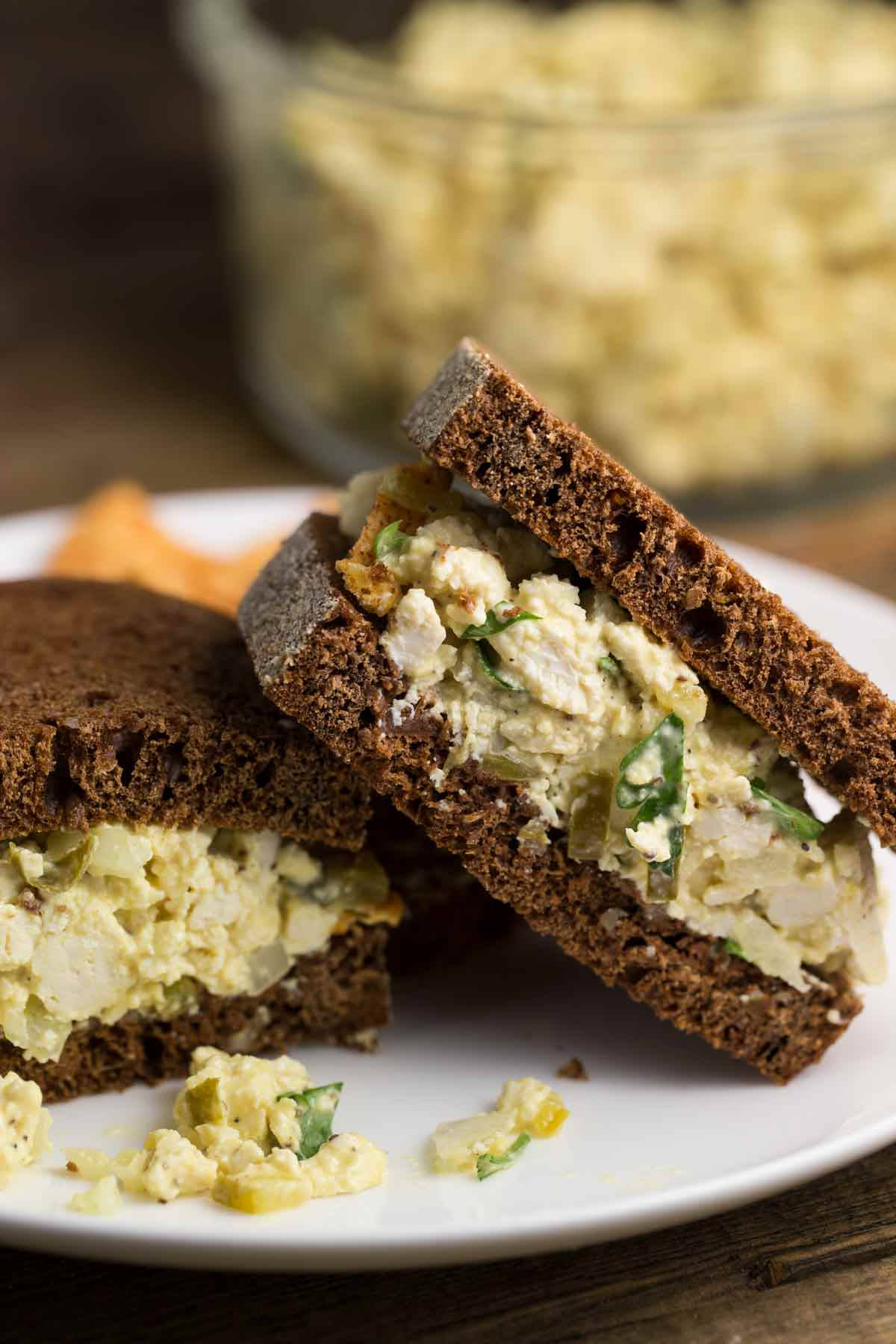 A vegan egg salad sandwich on pumpernickel bread, with chips on the side.