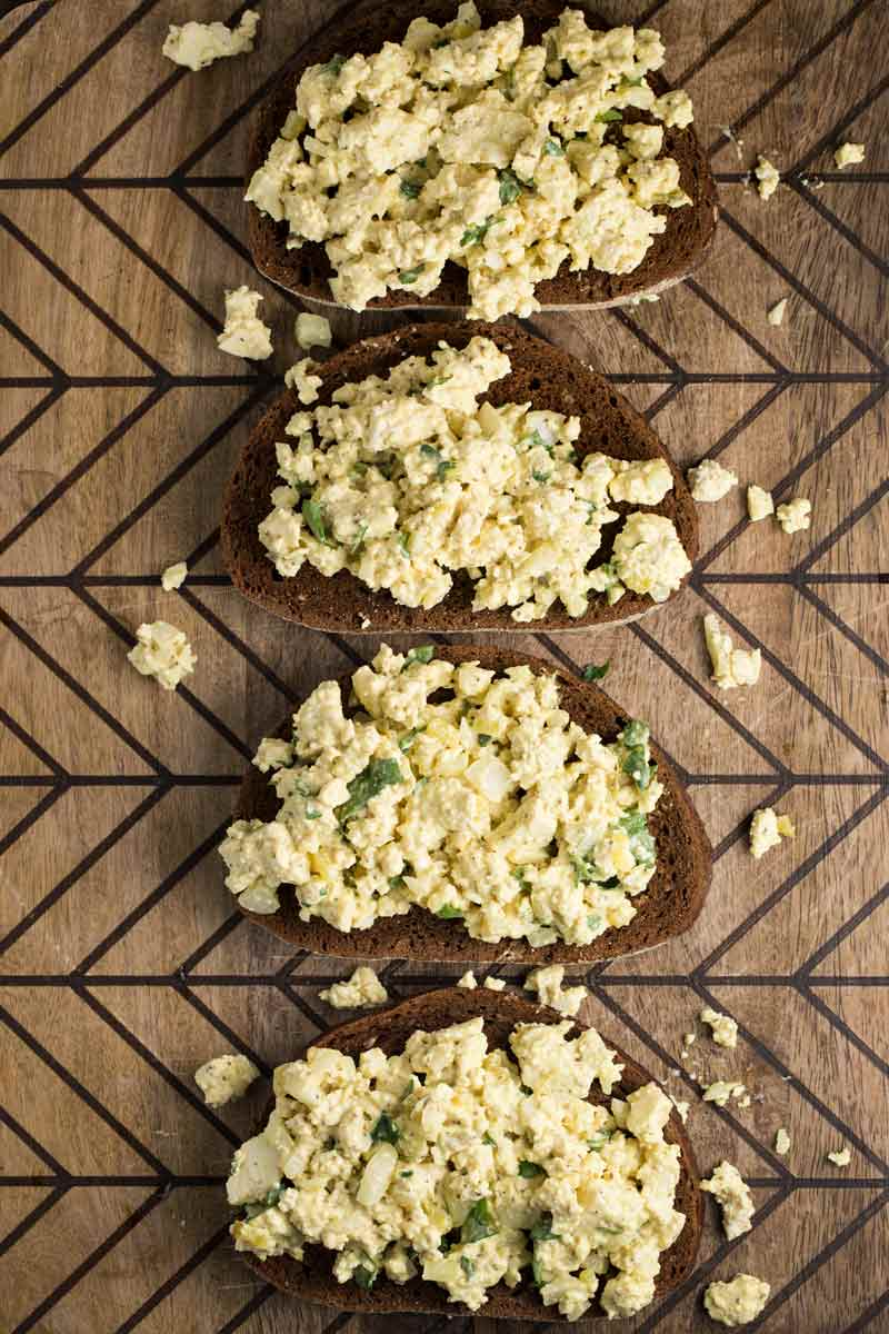 An overhead shot of a cutting board covered with bread with egg salad on top of each.