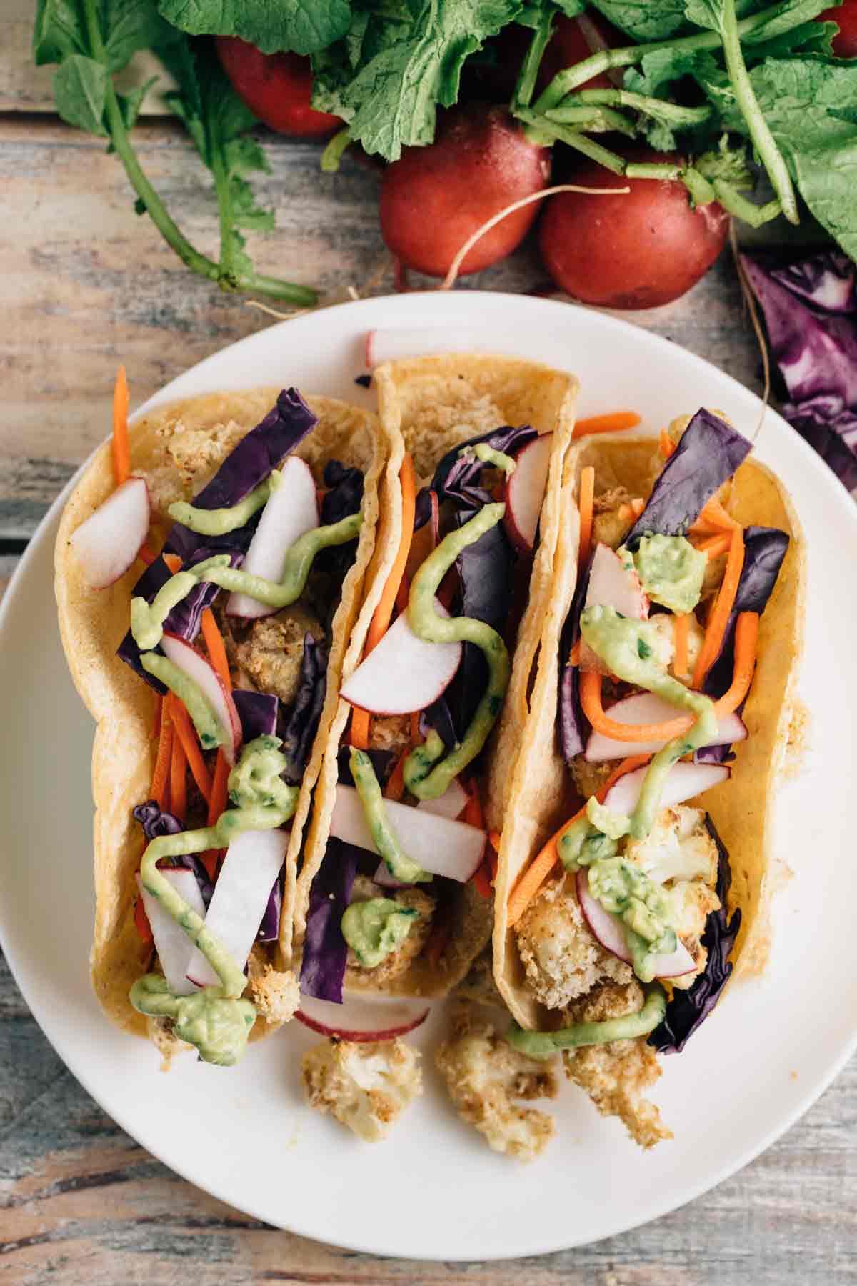 Crunchy Cauliflower Tacos w/ Avocado Lime Sauce | via veggiechick.com #vegan #glutenfree