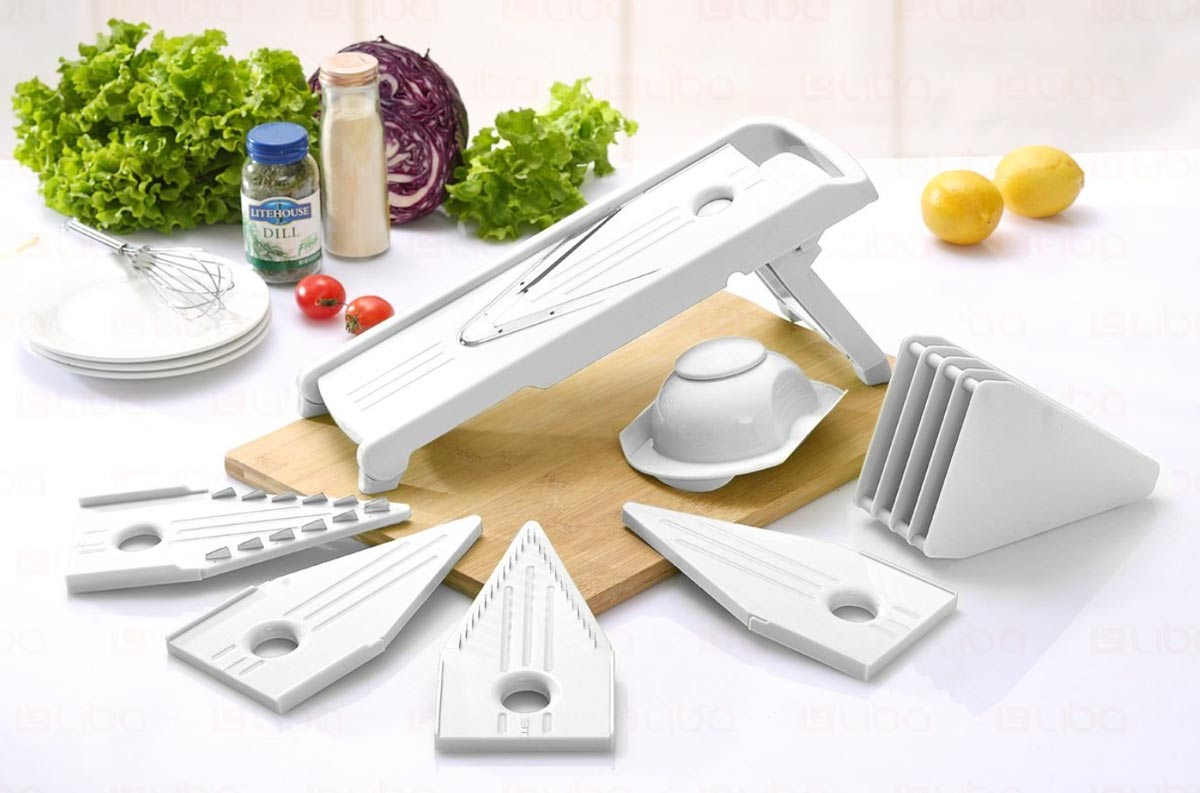 A mandoline slicer with many attachments surrounding it. You can see some vegetables in the background.