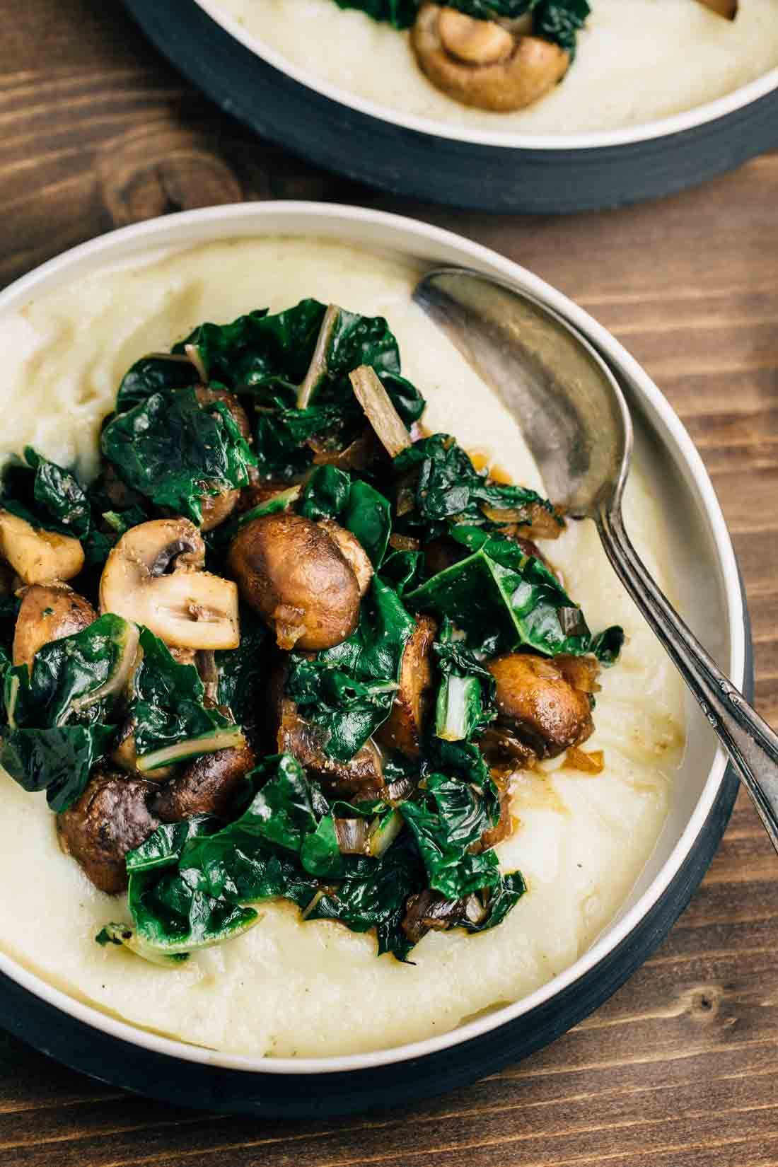 Cauliflower Puree with Sautéed Mushrooms and Swiss Chard in a black bowl.