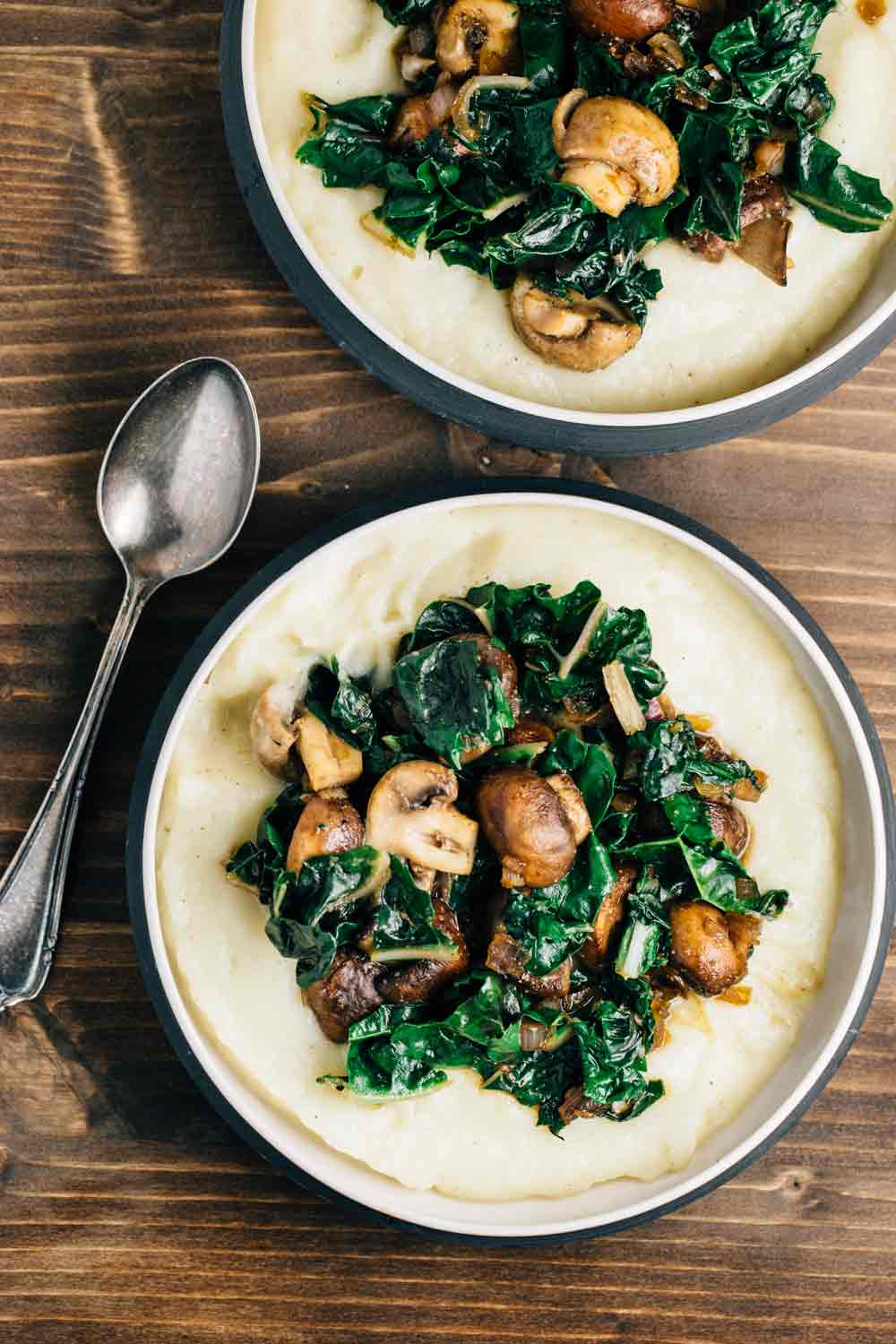 2 bowls of cauliflower puree with swiss chard and mushrooms.