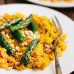 A plate of saffron rice asparagus with fork