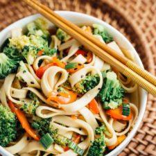 A bowl of sesame broccoli noodles with chopstick