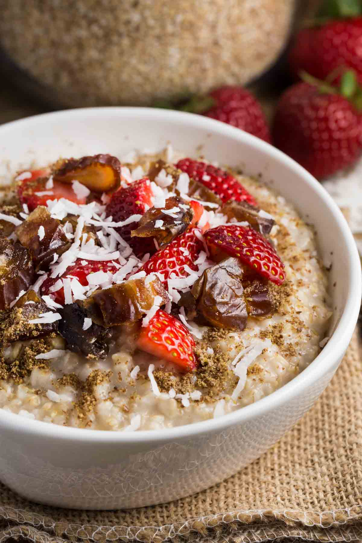 Bowl of steel cut oatmeal topped with dates, strawberries and coconut.