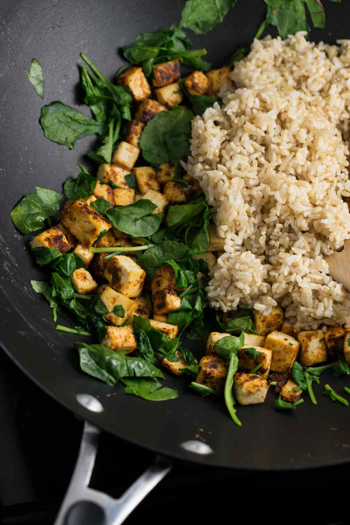 Closeup of rice, tofu and spinach being cooked in a wok.