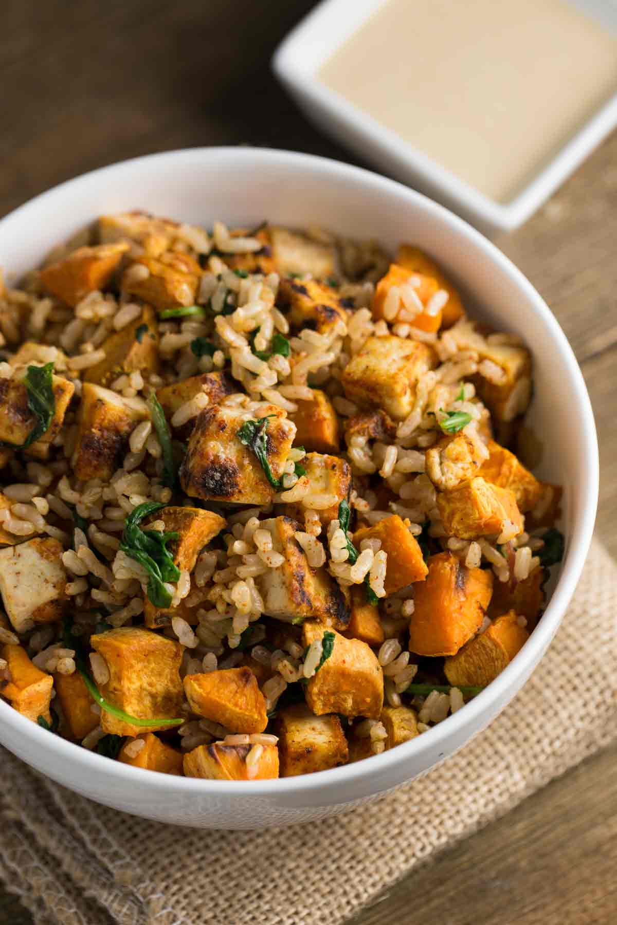 Tofu Sweet Potato Bowl with sweet tahini sauce on the side.