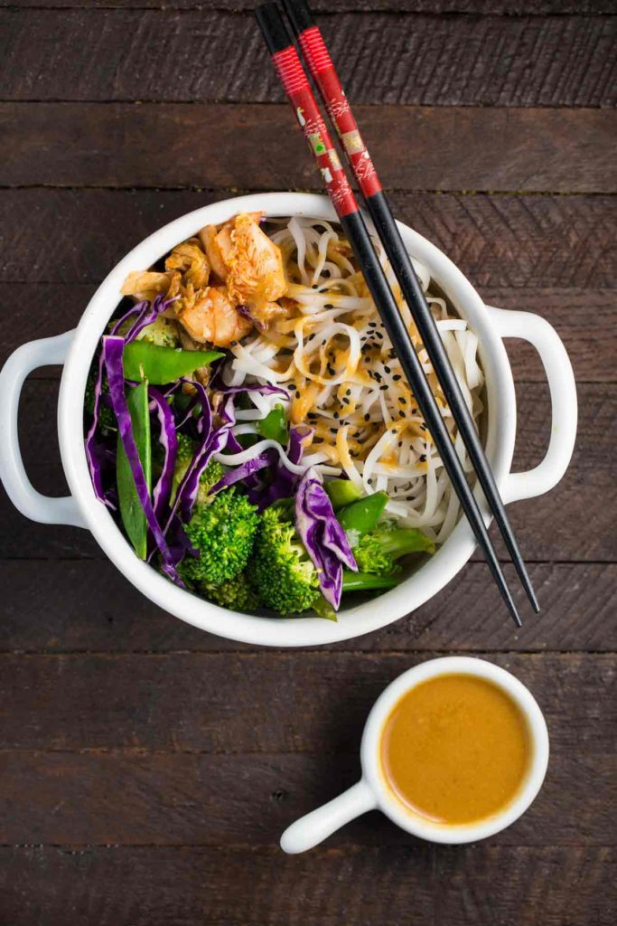 An overhead shot of cold noodle salad in a white bowl with chopsticks and a side of miso peanut sauce.