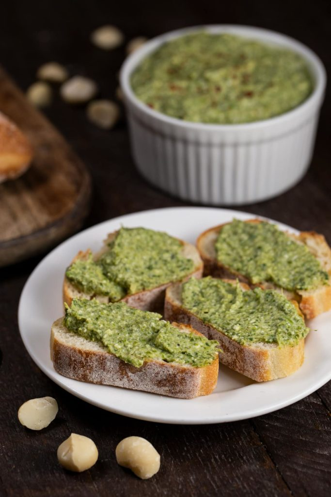 Spinach artichoke macadamia nut dip spread over pieces of toasted french bread slices.