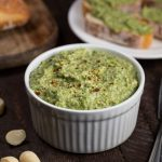 Spinach Artichoke dip with macadamia nuts all blended into a dip and served in a white bowl