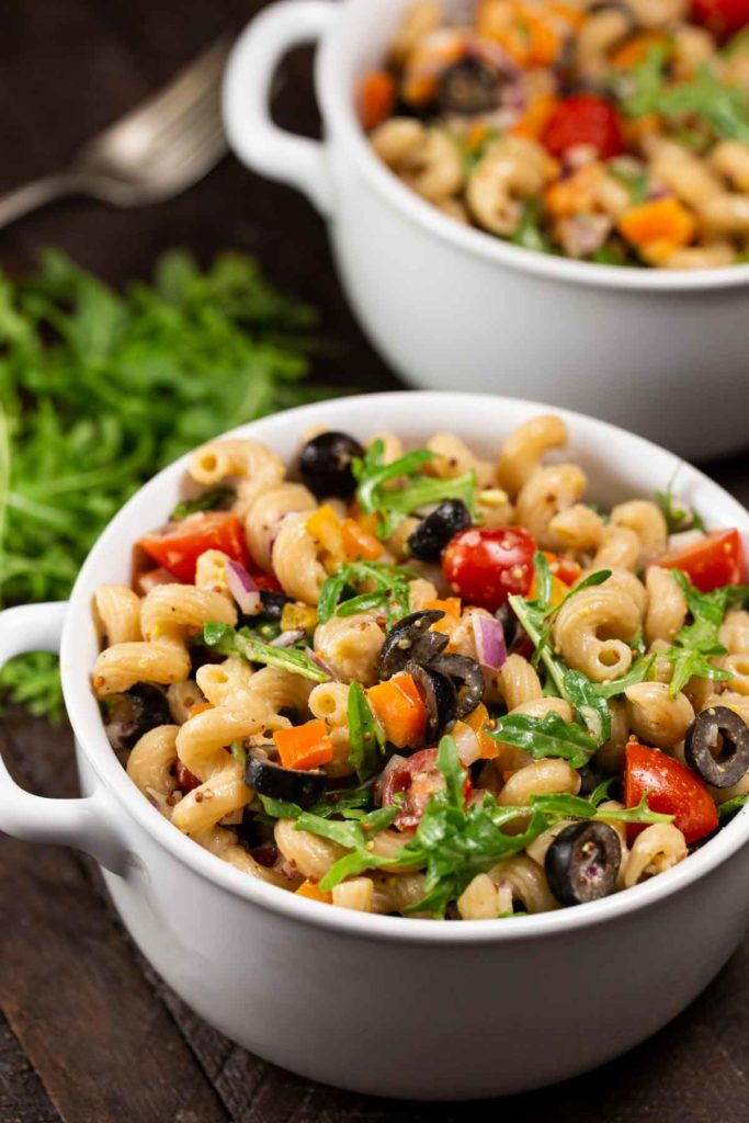 2 bowls of colorful pasta with a variety of veggies; cherry tomatoes, orange bell peppers, arugula, black olives, mixed with a fusilli (corkscrew) pasta. A pile of arugula and a fork in the background.