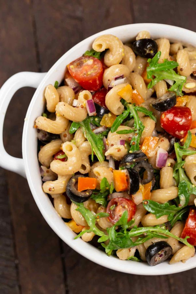 A bowl of pasta salad with colorful veggies; cherry tomatoes, red onion, sliced black olives, arugula, yellow pepper and a whole grain mustard sauce.