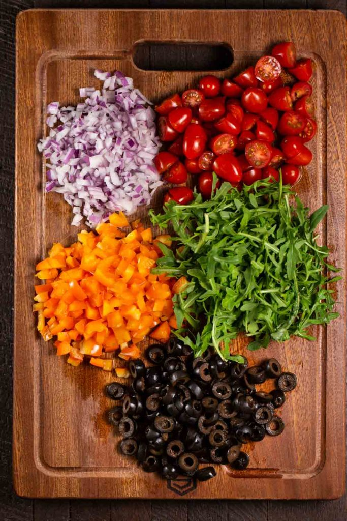 Chopped veggies on a cutting board.; red onion, orange pepper, cherry tomatoes, arugula, and black olives.