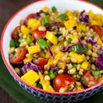 A colorful bowl filled with a mix of wheat berries, diced mango, cherry tomatoes, chopped jalapenos, red cabbage, and green onions.