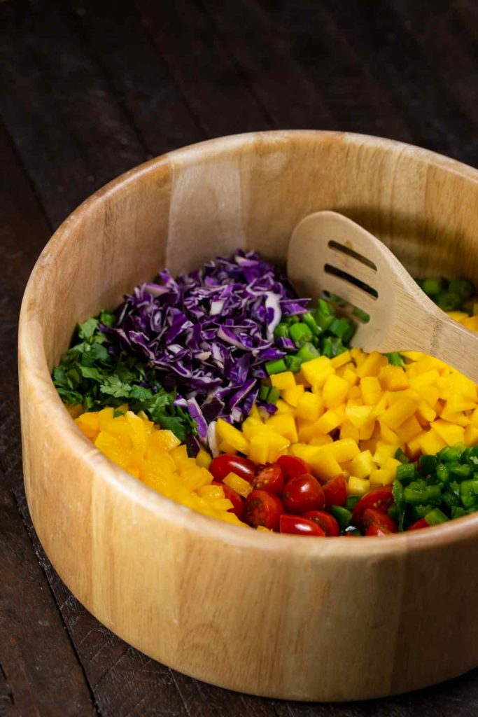 A bamboo bowl filled with chopped red cabbage, diced mangoes, chopped yellow pepper, cilantro, green onions and jalapenos.