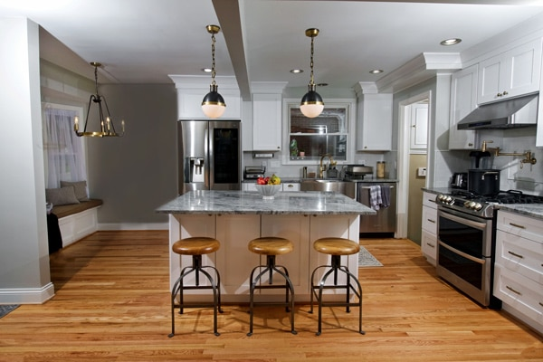 A newly renovated industrial chic kitchen with an island, pendant light and rustic stools.