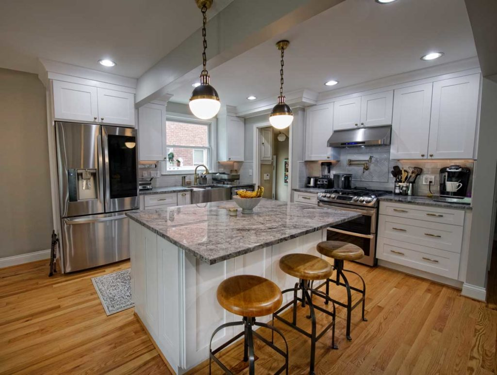 "An ""after"" photo of a kitchen redesign, showing a large island with 3 stools and quartzite countertops, and pendant lights hanging over the island, and white cabinets with champagne bronze hardware."