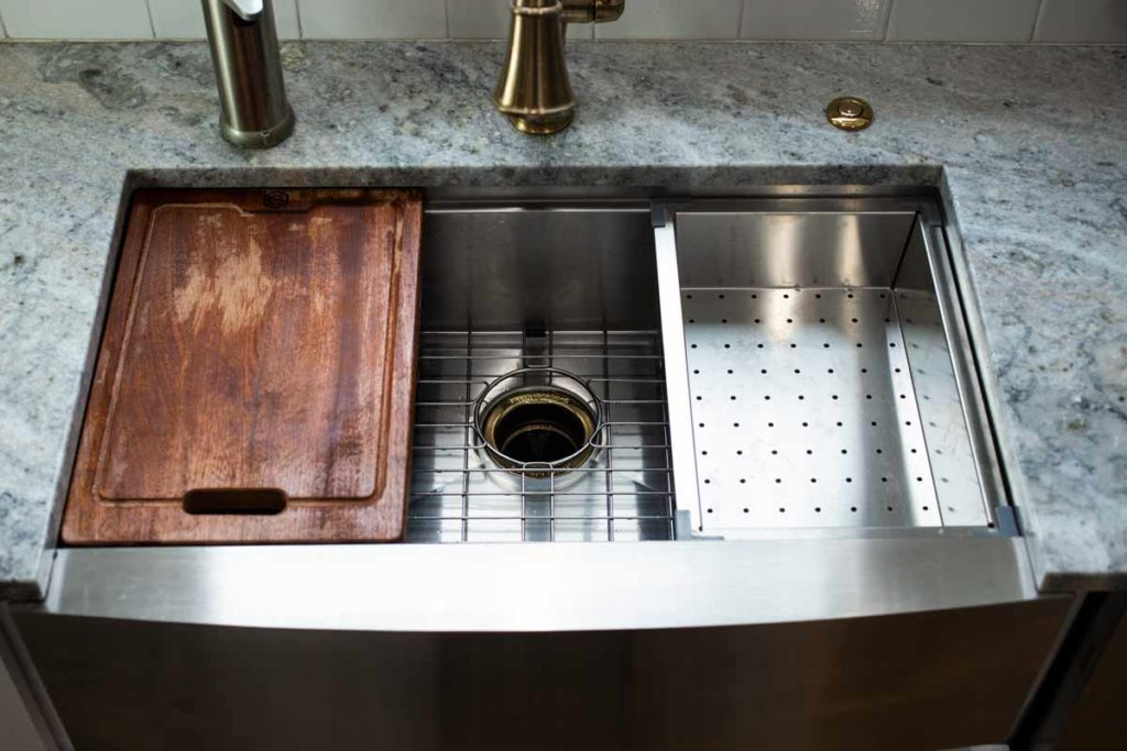 A stainless steel farmhouse sink with a cutting board and colander insert.