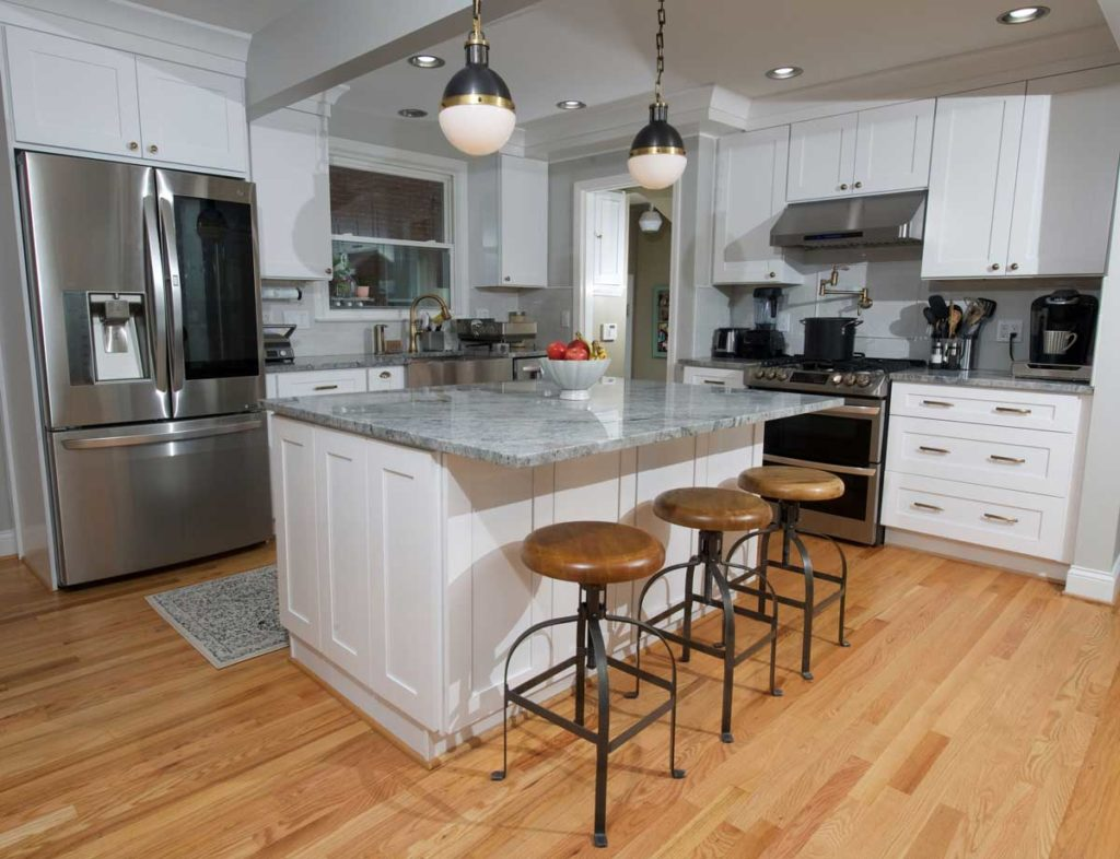 A brand new renovated white and gray kitchen, with beautiful pendant lights and 3 wooden stools.