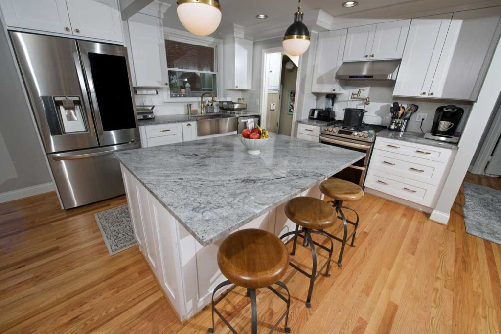 "A higher angle shot of an ""after"" photo of a kitchen redesign. You can see a large slab of fantasy gray quartzite with 3 wooden/metal stools pushed into the island, as well as white cabinets and a shiny new stainless steel fridge- with wood floors."