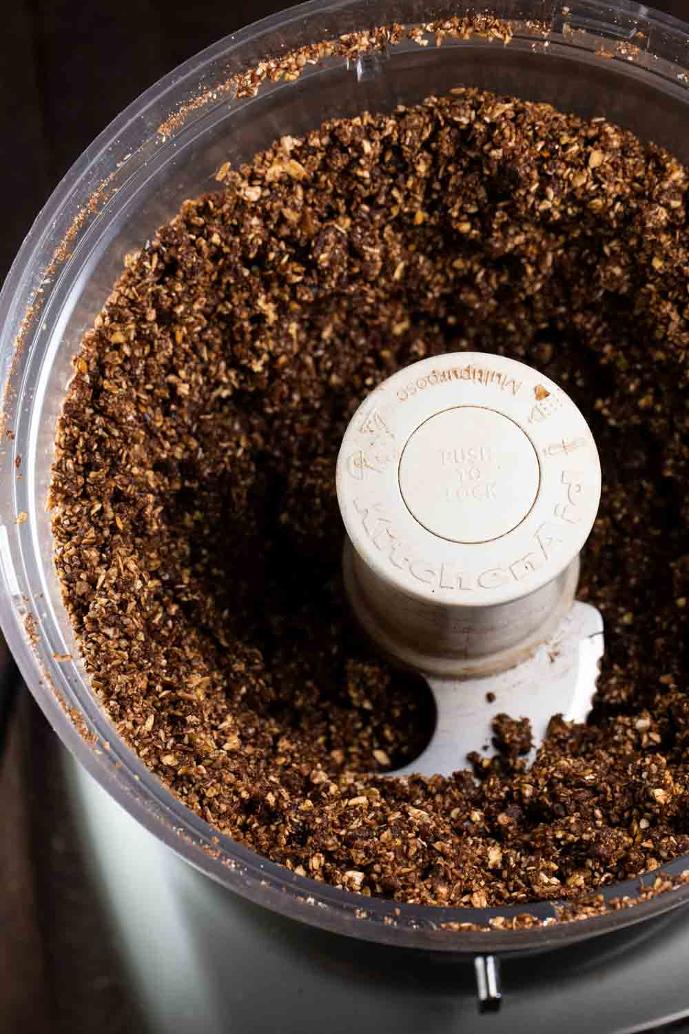 A food processor filled with a mix of almonds, cocoa, coconut oil, and flax seed.