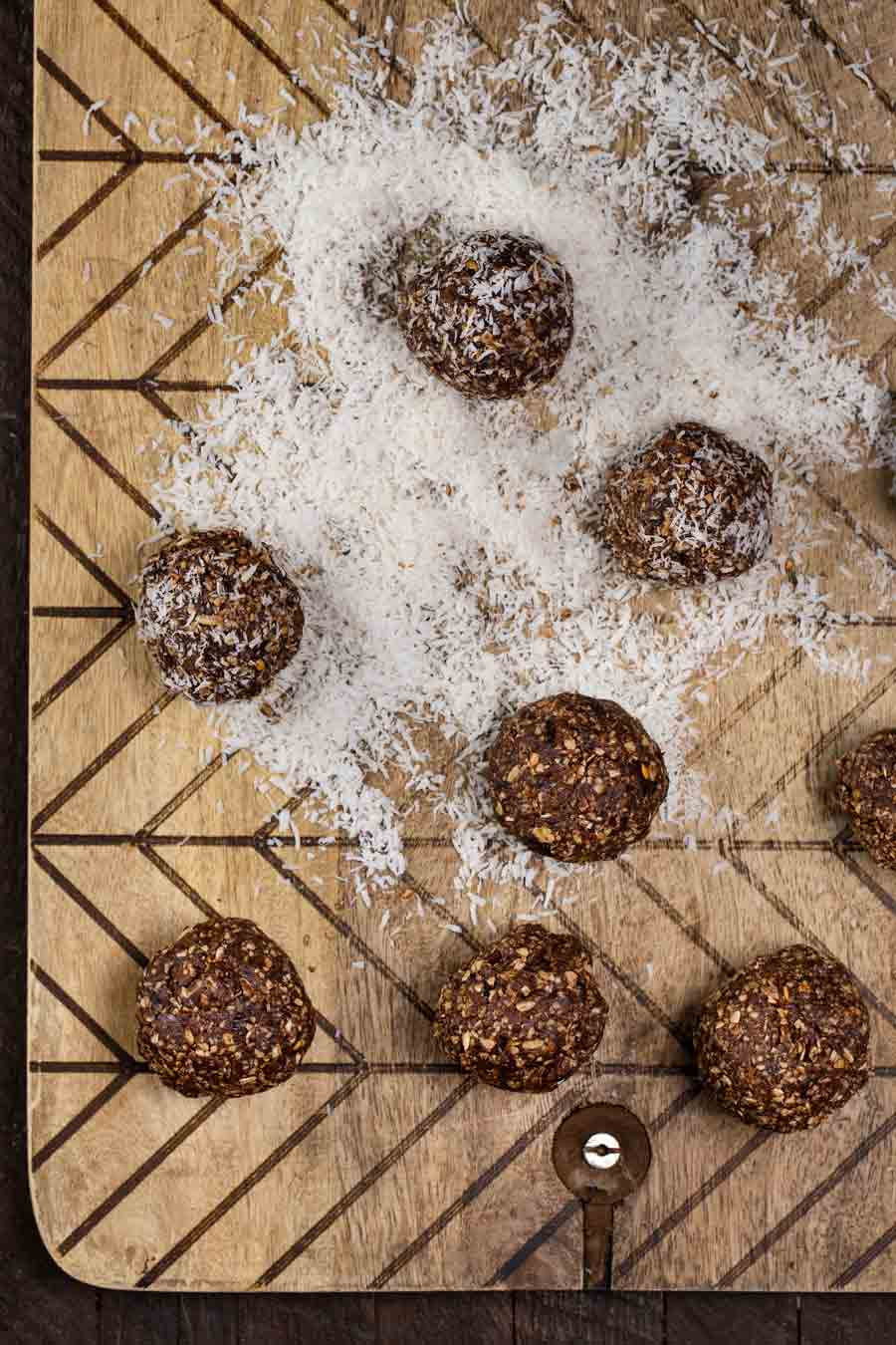 Chocolate Coconut No Bake Vegan Energy Balls on a cutting board, in unsweetened coconut flakes.