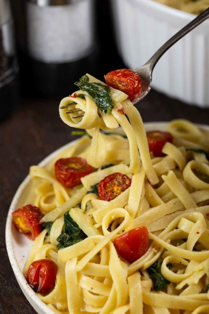 A plate of fettuccine noodles, with a closeup on the fork picking up a bite of the pasta, with twirled pasta, wilted spinach and a roasted cherry tomato in one bite.