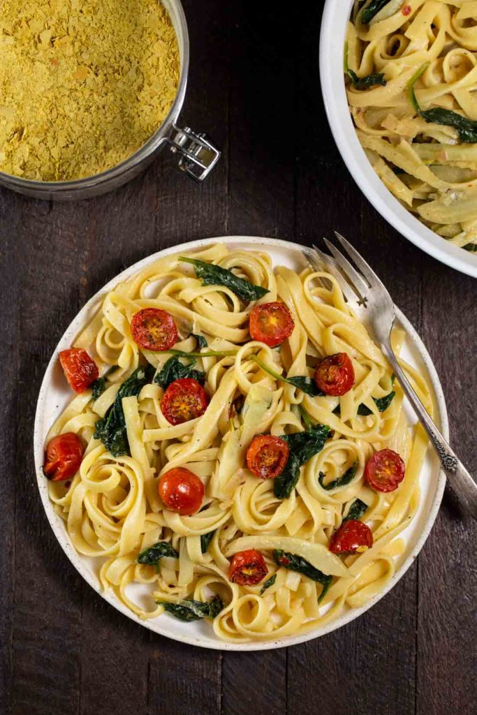 A high angle shot of a white plate of fettuccine covered with roasted tomatoes, wilted spinach and sliced fennel. You can also see a jar of nutritional yeast on the side.