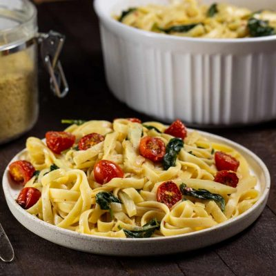 A plate of fettuccine noodles with roasted tomatoes, spinach and fennel. You can also see a jar with nutritional yeast and a white Corningware dish filled with the remaining pasta in the background.