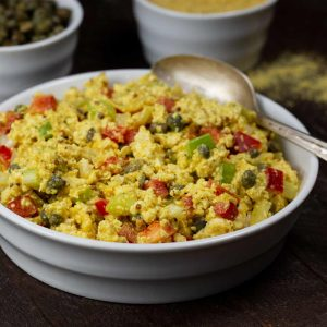 A bowl of vegan egg salad with colorful veggies such as capers, red peppers and celery. You can also see a bowl of capers and another bowl with nutritional yeast in the backgroud.