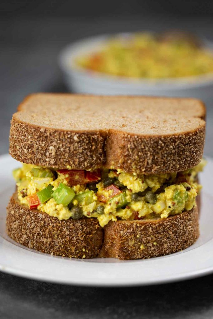 A closeup image of a white place with an egg salad sandwich with whole wheat bread on top.