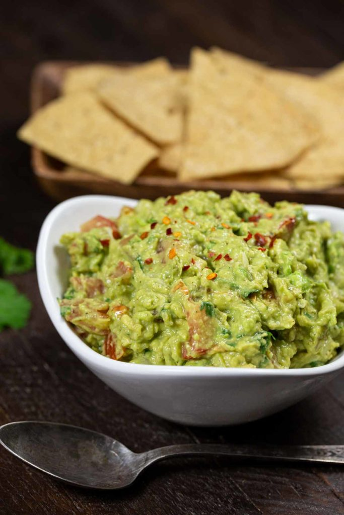 A white bowl filled with fresh guacamole with tomatoes, chopped cilantro and crushed red pepper, with some tortilla chips in the background.